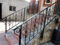 Металлические кованые перила для лестницы над входом в здание
