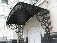 Металлический козырек над входной дверью с элементами ковки